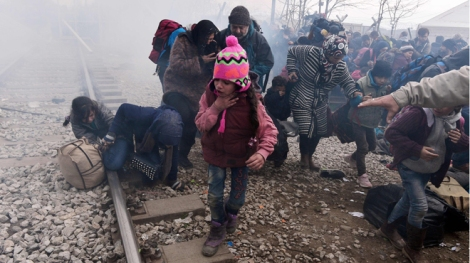 A child coughs as migrants and refugees run away after Macedonian police fired tear gas at hundreds of Iraqi and Syrian migrants who tried to break through the Greek border fence in Idomeni, on February 29, 2016. Greek police said more than 6,000 people were massed at the border, in a buildup triggered by Austria and Balkan states capping the numbers of migrants entering their territory. / AFP / LOUISA GOULIAMAKI